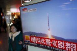 Una persona camina junto a una pantalla de televisor que muestra una noticia sobre el lanzamiento de un cohete de largo alcance por parte de Corea del Norte, en una estación de trenes en Seúl, Corea del Sur